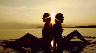 stock-footage-silhouettes-of-two-women-sitting-next-to-each-other-at-sunset (1)